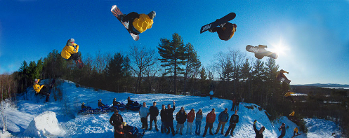Snowboarder jumping above crowd